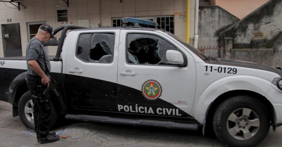 13.nov.2013 - Carro da Polícia Civil do Rio de Janeiro é atingido por tiros e pedradas na manhã desta quarta-feira (13) durante uma operação no complexo de favelas da Maré, na zona norte da cidade