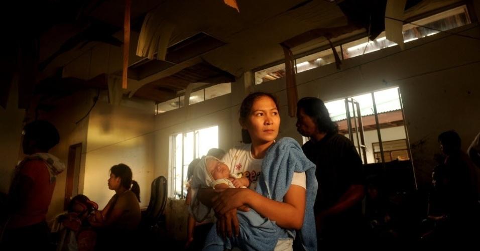 13.nov.2013 - Lina Mimbrello, 28, segura seu bebê de duas semas de vida enquanto aguarda para embarcar em avião militar para sair de Tacloban, cidade devastada pelo tufão Haiyan nas Filipinas, nesta quarta-feira (13)