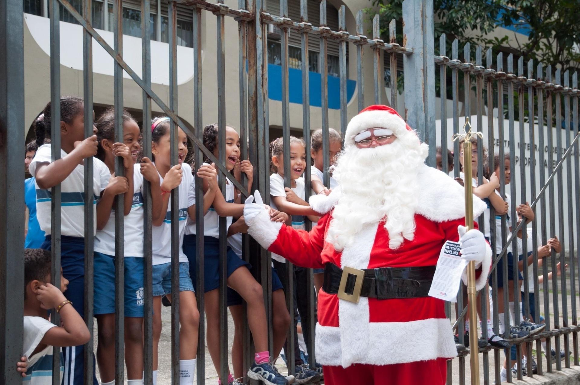 13.nov.2013 - Papai Noel que participava de protestos de advogados trabalhista na sede do Tribuna Regional do Trabalho (TRT), no centro do Rio de Janeiro, faz a alegria da criançada de escola municipal em frente ao local, na manhã desta quarta-feira (13)