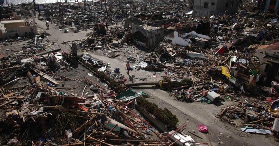 14.nov.2013 - Pessoas andam sobre os escombros de casas após passagem do tufão Haiyan, em Tanauan (Filipinas)