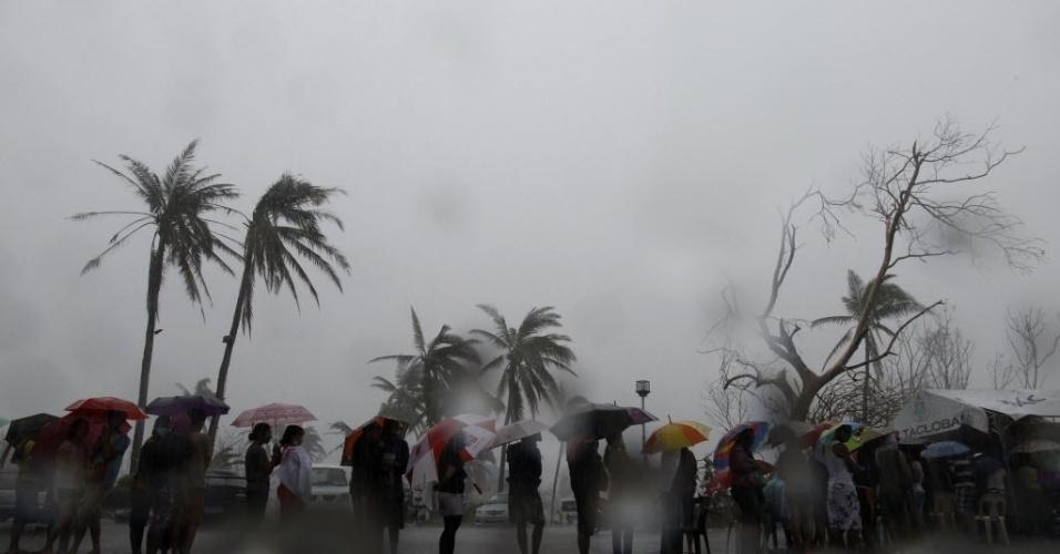 14.nov.2013 - 14.nov.2013 - Moradores de Tacloban enfrentam chuva forte enquanto esperam em fila para carregar as baterias de seus telefones celulares com gerador fornecido pela prefeitura da cidade