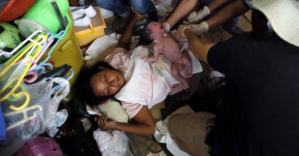 14.nov.2013 - Paramédicos ajudam Idara Marelo, 41, que acaba de dar à luz seu bebê em um abrigo temporário em Tacloban, Filipinas. Integrantes da organização humanitária Médicos Sem Fronteiras afirmaram que muitas vítimas do tufão Haiyan não têm recebido ajuda ainda devido a problemas logísticos