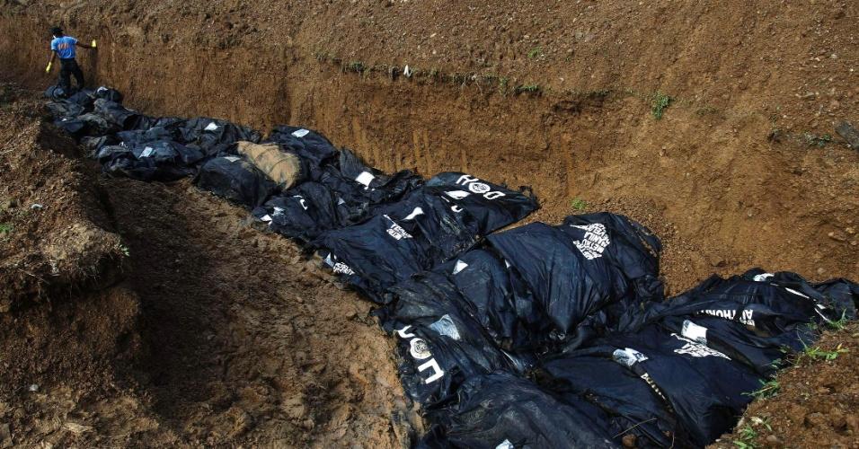 14.nov.2013 - Policial ajuda a mover os corpos para o enterro em uma vala comum de vítimas do tufão Haiyan na cidade de Tacloban, Filipinas. A prefeitura da cidade calcula que já recuperou quase 2.000 corpos