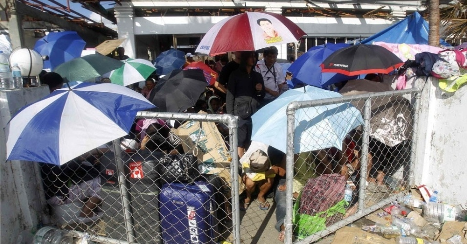 14.nov.2013 - Sobreviventes do tufão Haiyan esperam do lado de fora do portão para serem levados de helicóptero de Tacloban até Manila, Filipinas