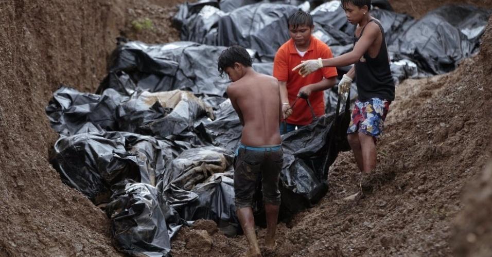 14.nov.2013 -Trabalhadores filipinos ajudam a mover os corpos para o enterro em uma vala comum de vítimas do tufão Haiyan na cidade de Tacloban, Filipinas. A prefeitura da cidade calcula que já recuperou quase 2.000 corpos