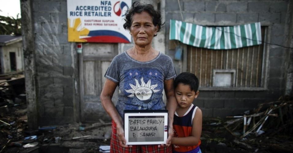 Uma mulher escreve o nome dela e da criança em um tablete na província de Samar, nas Filipinas, para pedir ao fotógrafo John Javellana que poste nas redes sociais, assim seus familiares poderiam saber que eles estão vivos