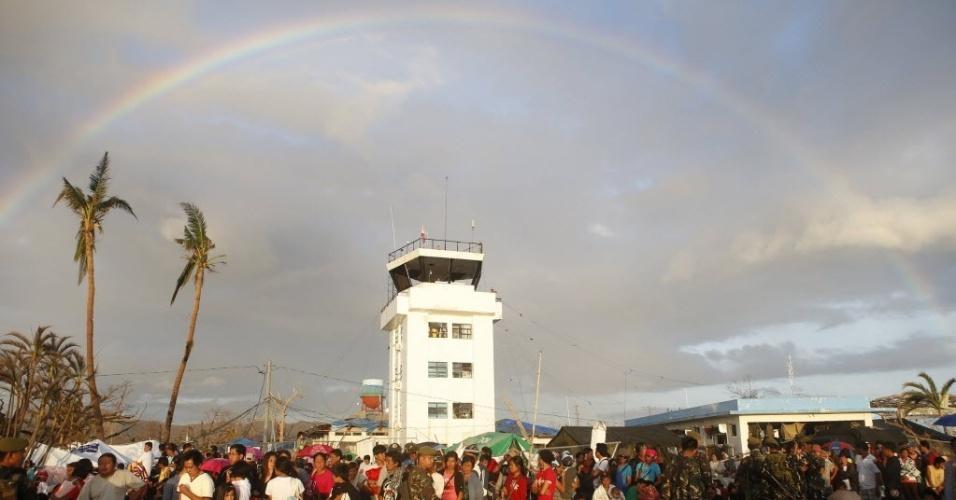 15.nov.2013 - Arco-íris corta o céu de Tacloban (Filipinas) --a cidade mais afetada pela passagem do tufão Haiyan pelo país, há quase uma semana-- enquanto sobreviventes se preparam para deixar a cidade, no aeroporto de Tacloban