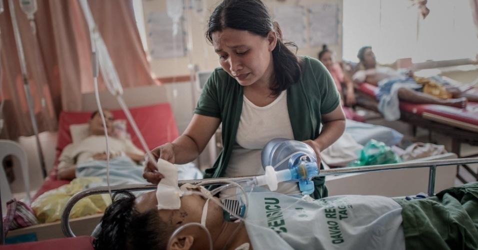 15.nov.2013 - Filipina mantém seu marido vivo ao bombear ar manualmente para seus pulmões nesta sexta-feira (15) em um hospital de Tacloban, nas Filipinas. Ele se feriu durante a passagem do supertufão Haiyan pelo país. A cidade foi uma das mais afetadas e sofre com a falta de estrutura e de recursos