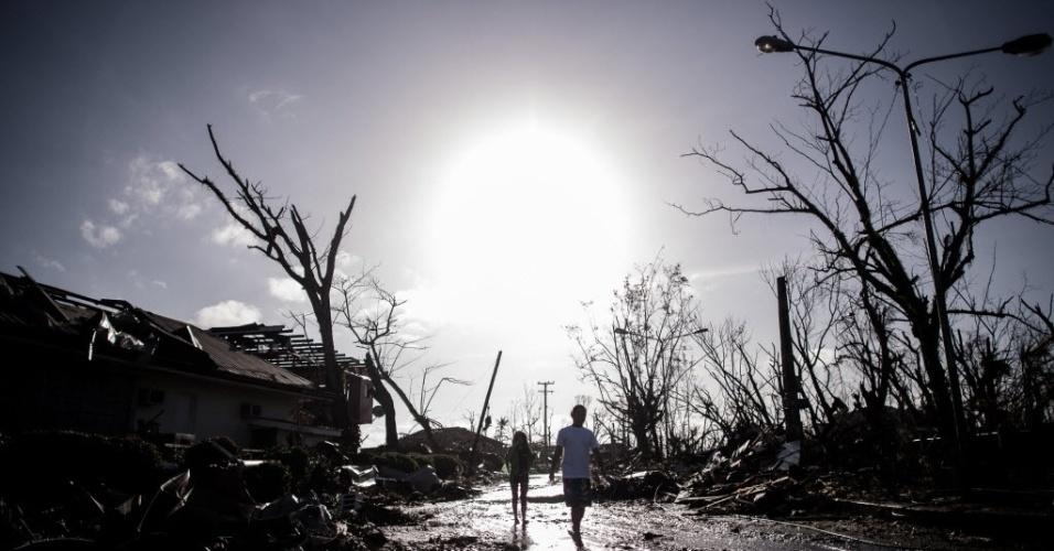 15.nov.2013 - Moradores da cidade de Tacoblan, nas Filipinas, caminham por entre os destroços de casas após a passagem do tufão Haiyan. Estimativas da ONU apontam que 10 mil pessoas teriam morrido na região