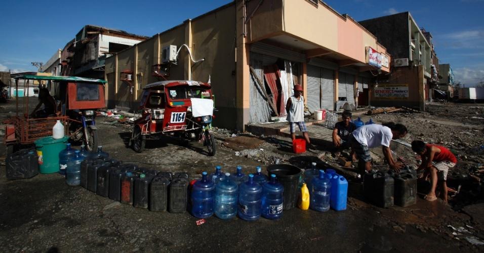 15.nov.2013 - Moradores de Tacloban ---a cidade mais afetada pelo tufão Haiyan, que devastou o país há uma semana -- retiram água de tubulação subterrânea e estocam em garrafões