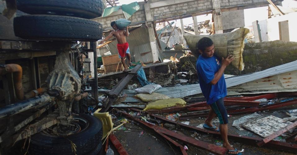 15.nov.2013 - Moradores de Tacloban --a cidade mais afetada pelo tufão Haiyan, que devastou as Filipinas há uma semana-- carregam sacos de arroz retirados de armazém destruído pela força dos ventos, de até 300 km/h