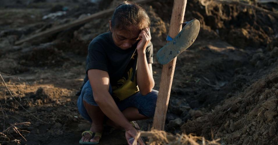 15.nov.2013 - Mulher de 37 anos chora próximo ao túmulo do marido que morreu durante a passagem do tufão Haiyan em Tacloban, nas Filipinas