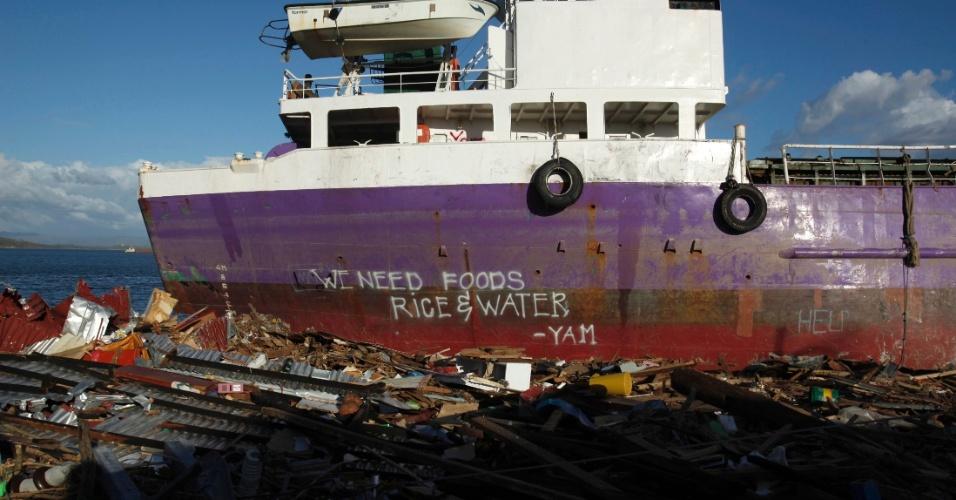 15.nov.2013 - Sobreviventes  de tufão solicitam ajuda e comida com imagem pintada em casco de navio em Tacloban, nas Filipinas