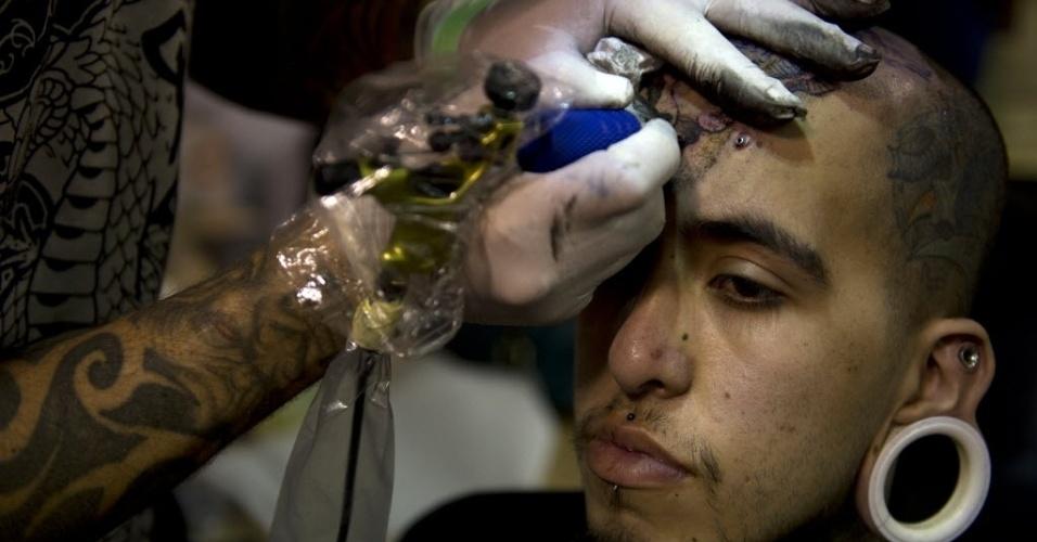 15.nov.2013 - Um tatuador desenha sobre a testa de um cliente na Bogota Tattoo Convention, em Bogotá, nesta sexta-feira (15). Cerca de 300 tatuadores de todo o mundo apresentam a sua arte na sétima edição do evento, que acontece entre 15 e 17 de novembro, e também conta com apresentações de dança e uma feira de roupas