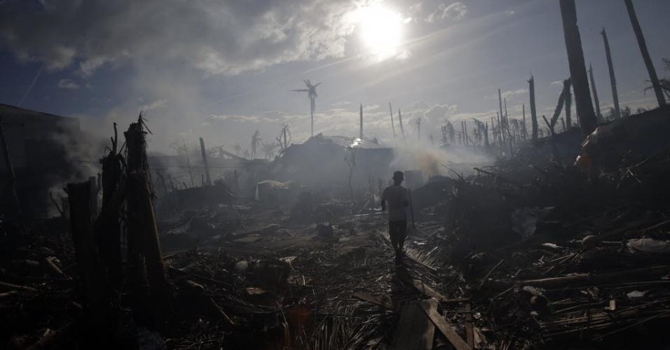 16.nov.2013 - Homem caminha em meio à fumaça de incêndios neste sábado (16), em uma região de Tolosa, nas Filipinas, que foi devastada pelo super tufão Haiyan. Doações de alimentos e água feitas por outros países começaram a chegar somente neste sábado
