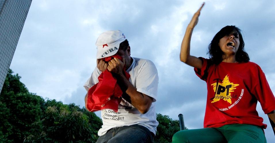 16.nov.2013 - Militante do PT chora em cima de cerca da sede da Polícia Federal em Brasília durante protesto contra a prisão dos condenados por participação no esquema que ficou conhecido como mensalão