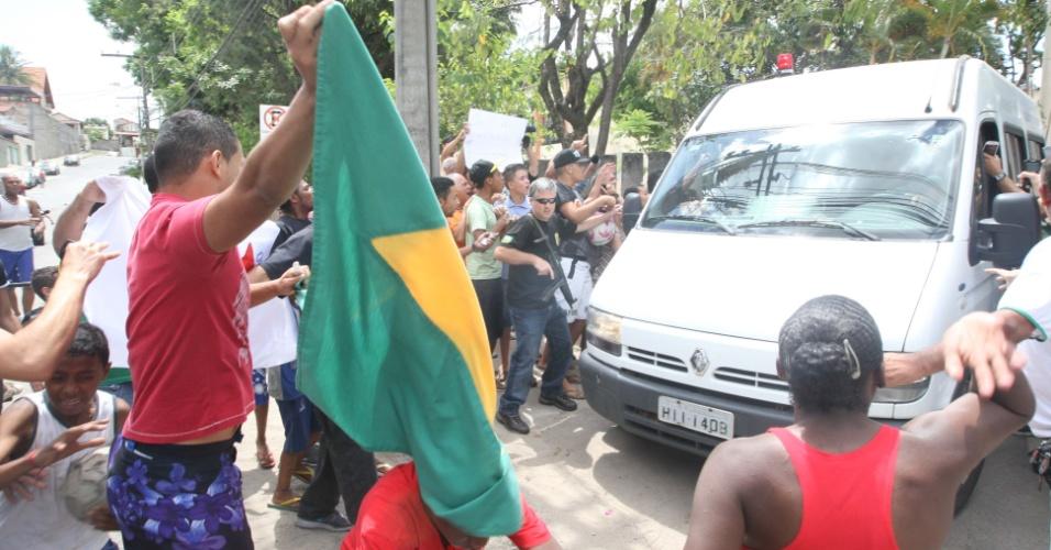 16.nov.2013 - Pessoas protestam do lado de fora do Instituto Médico Legal (IML), em Belo Horizonte (MG), enquanto as vãs que trazem os condenados do mensalão chegam ao local, neste sábado (15)