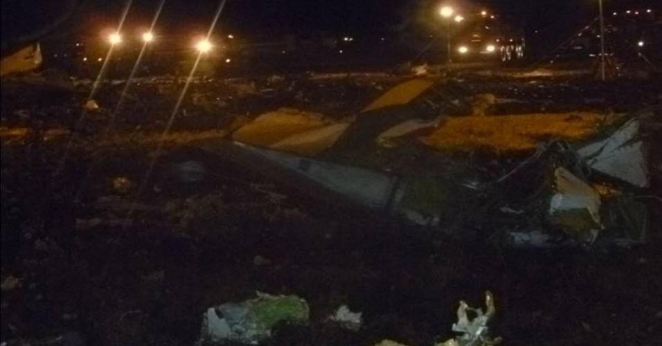 17.nov.2013 - Destroços são vistos no local onde um Boeing 737 pertencente à companhia aérea Tatarstan Airlines, que caiu matando ao menos 50 pessoas neste domingo (17), no aeroporto de Kazan, na Rússia, que fica a 720 km a leste de Moscou. O avião partiu do aeroporto de Domodedovo, em Moscou, e seguia para a cidade de Petrozavodsk. A área do acidente foi cercada e o aeroporto foi fechado