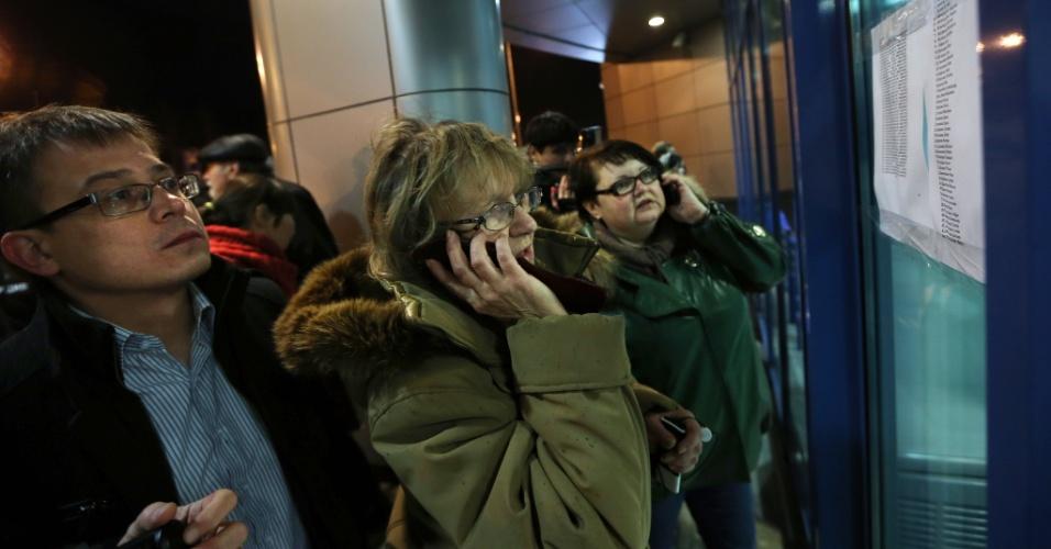 17.nov.2013 - Pessoas falam ao celular enquanto procuram nomes na lista dos passageiros mortos em acidente envolvendo um Boeing 737 pertencente à companhia aérea Tatarstan Airlines, que caiu matando ao menos 50 pessoas neste domingo (17). O avião partiu do aeroporto de Domodedovo, em Moscou, e seguia para a cidade de Petrozavodsk. A área do acidente foi cercada e o aeroporto foi fechado