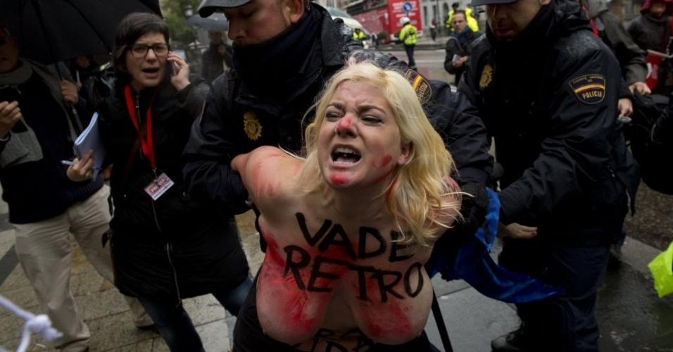 17.nov.2013 - Uma ativista do Femen, famoso por protestos com mulheres seminuas, é presa por um policial durante ato contra uma marcha anti-aborto em Madri (Espanha), neste domingo (17)