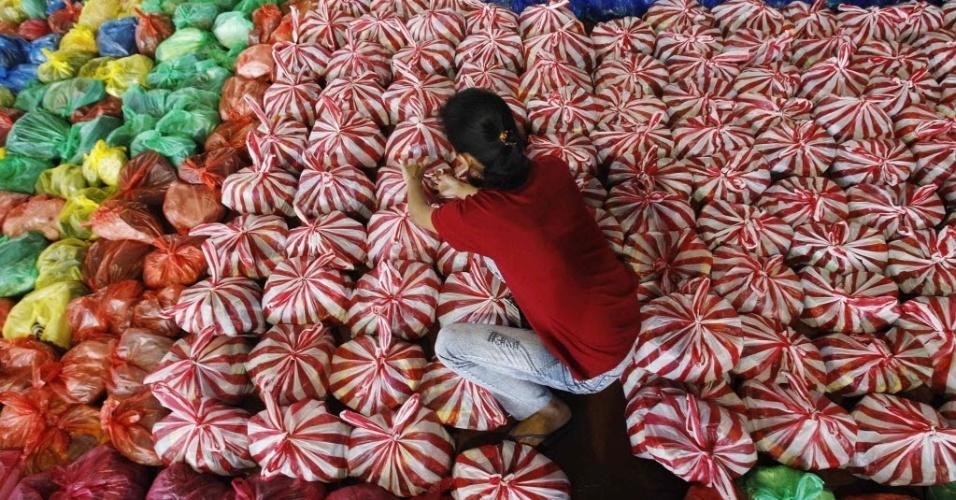 18.nov.2013 - Estudante prepara pacotes de socorro na Universidade Politécnica das Filipinas, em Manila. Muitas comunidades permanecem isoladas depois da passagem do tufão Haiyan no último dia 8