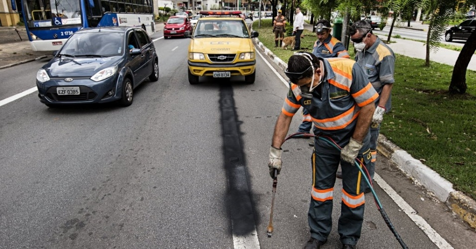 18.nov.2013 - Funcionários da prefeitura apagam sinalização da motofaixa desativada nesta segunda-feira (18) na avenida Sumaré, na zona oeste de São Paulo. No mesmo dia, uma faixa exclusiva para ônibus foi implantada na via. Segundo a CET (Companhia de Engenharia de Tráfego),