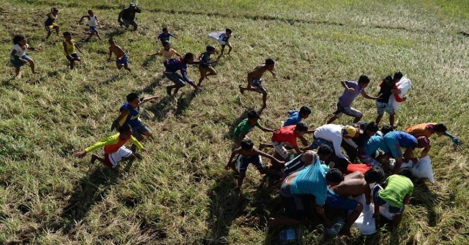 18.nov.2013 - Moradores da ilha de Leyte, devastada pelo tufão Haiyan, correm para pegar comida enviada por um helicóptero da Força Aérea das Filipinas. O país deve receber uma ajuda de US$ 1 bilhão para reconstruir as áreas destruídas