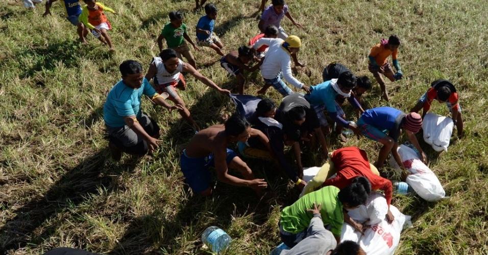 18.nov.2013 - Moradores da ilha de Leyte, devastada pelo tufão Haiyan, correm para pegar alimentos enviados por um helicóptero da Força Aérea das Filipinas. O país deve receber uma ajuda de US$ 1 bilhão para reconstruir as áreas destruídas