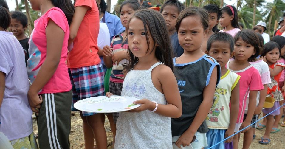 19.nov.2013 - Crianças fazem fila para receber comida em estrada de Hernani, na região central das Filipinas