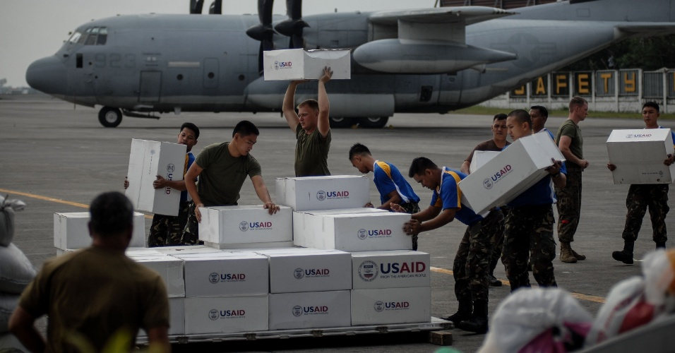 19.nov.2013 - Soldados americanos e filipinos descarregam mantimentos em Tacloban, Filipinas