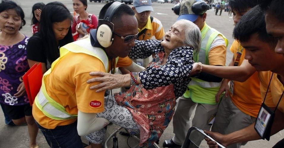 19.nov.2013 - Sobreviventes ajudam idosa a embarcar em avião no aeroporto de Tacloban, nas Filipinas. As autoridades aumentaram para 3.976 o número provisório de mortos provocados pelo tufão Haiyan na região central do país