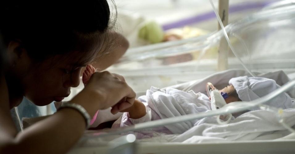 20.nov.2013 - Mãe de bebê nascido prematuro toca com a testa o pé de sua filha em maternidade de centro médico de Tacloban, nas Filipinas, nesta quarta-feira (20).  Crianças com diversos tipos de lesões e bebês recém-nascidos lotam o espaço limitado do hospital, gravemente danificado pelo tufão Haiyan