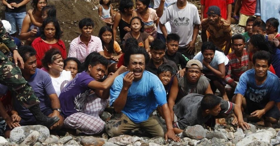 20.nov.2013 - Moradores de vila destruída pelo tufão Haiyan reagem com a chegada de helicóptero dos EUA trazendo ajuda em Guiuan, nas Filipinas, nesta quarta-feira (20). A coordenadora humanitária da ONU, Valerie Amos, afirmou que os desafios atuais são garantir o acesso à água potável, a montagem de abrigos de emergência e a proteção básica para mulheres e crianças em uma região onde mais de 500 mil casas ficaram completamente destruídas