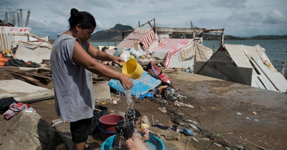 21.nov.2013 - Mulher da banho nos filhos em alojamento temporário em Tacloban, Filipinas. A organização Médicos Sem Fronteiras insistiu nesta quinta-feira que a ajuda humanitária ainda não chegou a centenas de vítimas nas áreas mais remotas do país