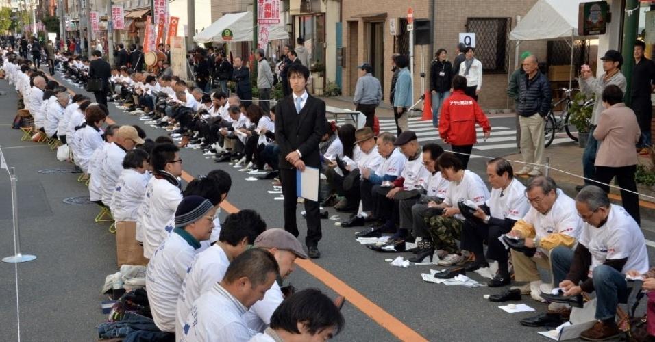 """22.nov.2013 - Cerca de 800 participantes engraxam sapatos em uma rua de Tóquio, Japão, para tentar  alcançar o recorde de """"o maior número de pessoas polindo sapatos"""". Os participantes estabeleceram um novo recorde mundial em relação à anterior, feito com 451 pessoas nos Emirados Árabes Unidos em 2011, e entraram para o Guinness Book, o livro dos recordes"""
