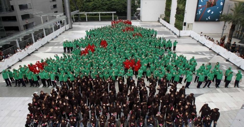 """22.nov.2013 - Oitocentos e cinquenta e dois estudantes se reúnem para quebrar o recorde de """"a maior árvore de Natal humana"""", na área externa de um shopping center em Bangcoc, Tailândia. O recorde anterior foi obtido pela Alemanha em 2011 e contou com 672 pessoas"""