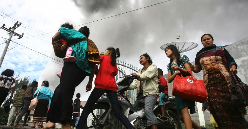 24.nov.2013 - Moradores da vila Aman Teran, em Karo, na Indonésia, levam pertences para centro de evacuação depois que o vulcão Monte Sinabung voltou a expelir cinzas neste domingo (24)