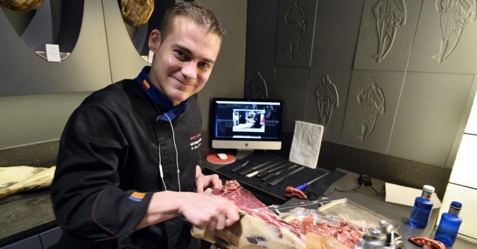 25.nov.2013 - Especialista em presunto, o espanhol Noe Bonillo Ramos corta um presunto Pata Negra durante um desafio de 25 horas para quebrar o recorde do Guinness, em uma loja especializada em presuntos, em Paris