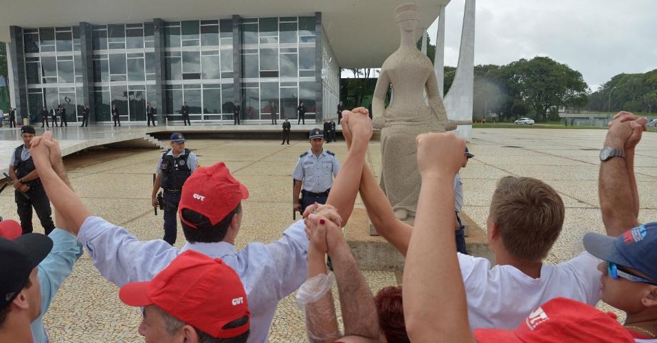 26.nov.2013 - Manifestantes da Central Única dos Trabalhadores (CUT) fazem protesto em frente ao Supremo Tribunal Federal (STF) contra a prisão de José Dirceu, José Genoino e Delúbio Soares