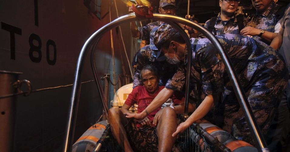 """26.nov.2013 - Médicos militares chineses acomodam sobrevivente ferido em bote salva-vidas para ser içado até o navio-hospital Peace Ark (""""Arca da Paz""""), na costa de Leyte (Filipinas) --região mais afetada pela passagem do tufão Haiyan, há quase três semanas"""