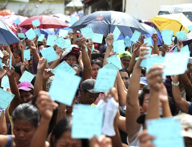 26.nov.2013 - Vários cidadãos mostram vouchers para trocar por comida na cidade devastada de Tacloban, Filipinas. O governo filipino está planejando grandes mudanças na infraestrutura após o desastre causado pelo tufão Haiyan