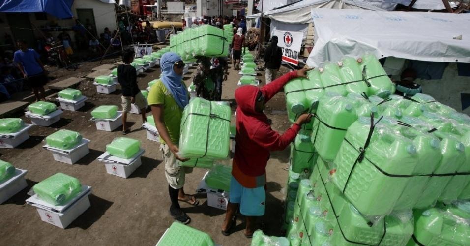26.nov.2013 - Voluntários da Cruz Vermelha preparam a distribuição de galões de água na cidade de Tacloban, nas Filipinas. O governo filipino está planejando grandes mudanças na infraestrutura após o desastre causado pelo tufão Haiyan