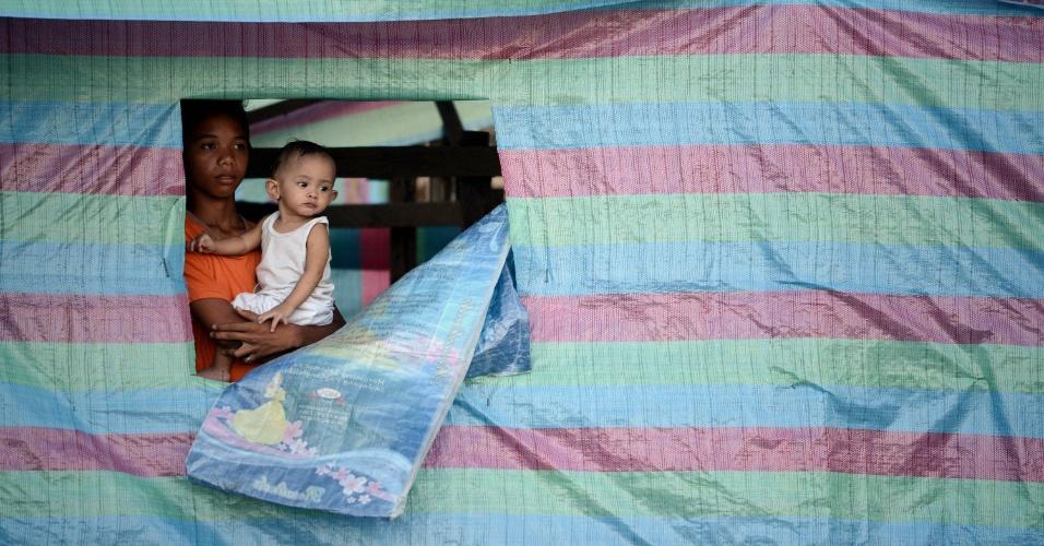 27.nov.2013 - Um menino segura seu irmão em uma casa improvisada na baía de Tacloban, na província de Leyte, nas Filipinas