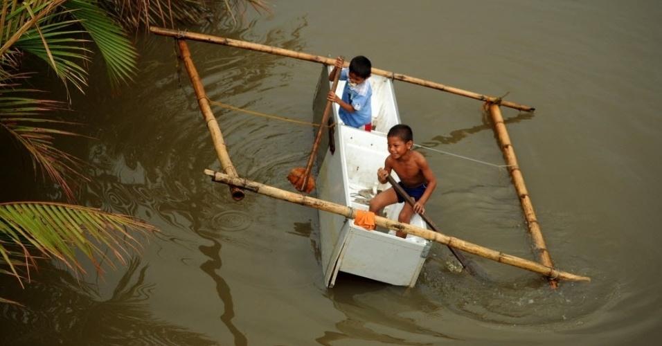 28.nov.2013 - Crianças usam geladeira como barco para atravessa um rio em Samar, Filipinas. O número de mortos na região subiu para 5.500. Autoridades estimam que 9,9 milhões de pessoas foram afetadas pelo tufão em 574 municípios, e que 225.922 deles estejam alojados em 1.069 centros de evacuação