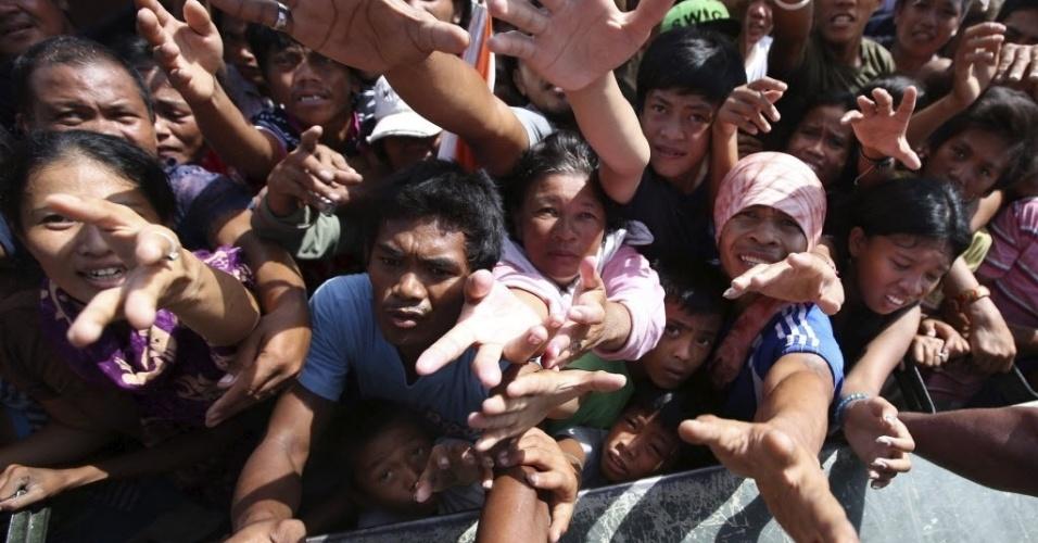 28.nov.2013 - Multidão de sobreviventes do tufão Haiyan se reúne em torno de voluntários que entregam donativos na área devastada de Tacloban, Filipinas. O número de mortos pela passagem do tufão subiu para 5.500. Autoridades estimam que 9,9 milhões de pessoas foram afetadas pelo tufão em 574 municípios, e que 225.922 deles estejam alojados em 1.069 centros de evacuação