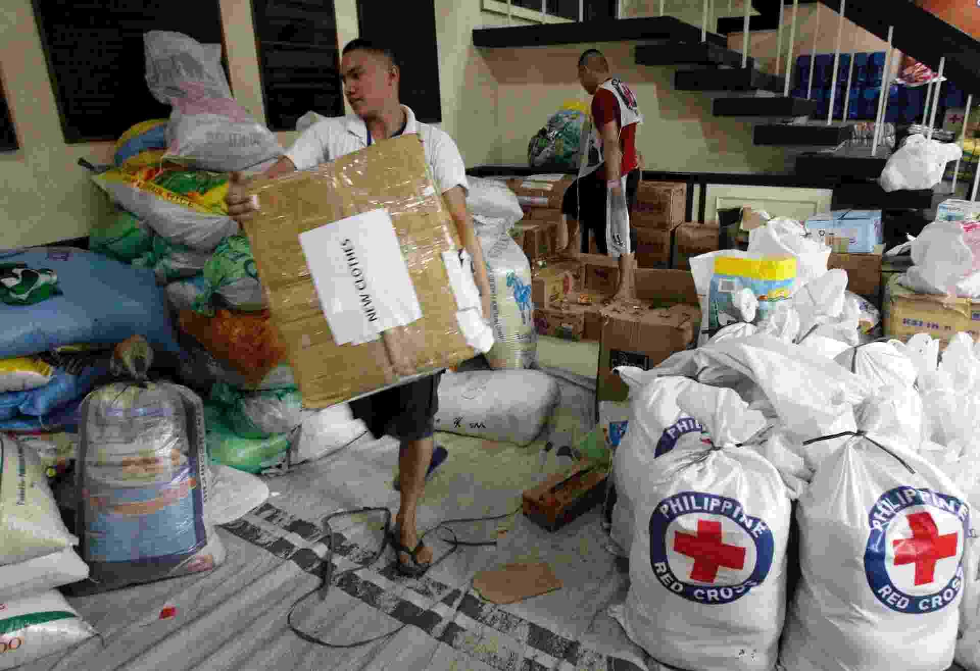 28.nov.2013 - Voluntário carrega donativos que serão transportados para regiões afetadas pelo tufão Haiyan, nas Filipinas, dentro de centro de distribuição da Cruz Vermelha - Romeo Ranoco/Reuters