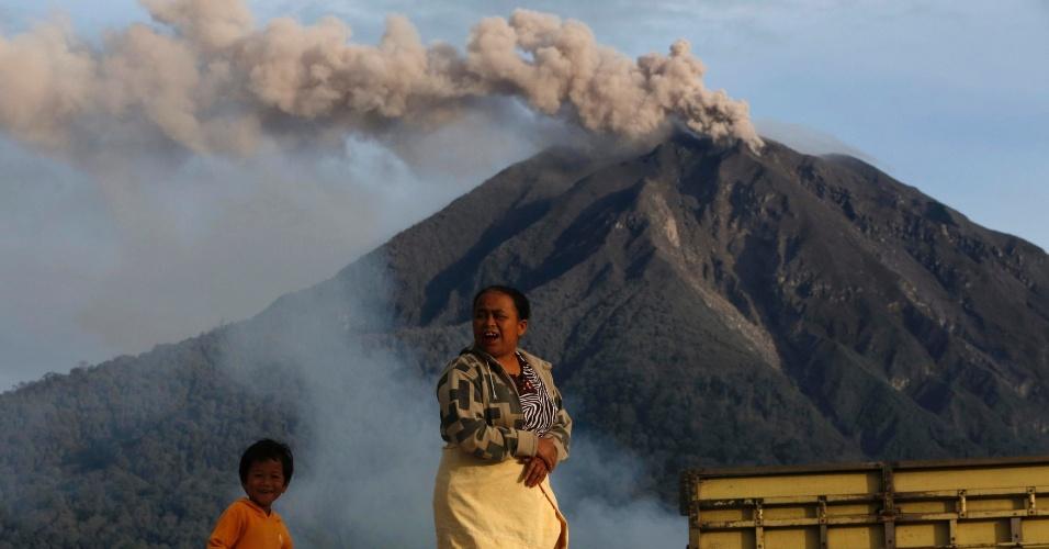 29.nov.2013 - Mulher caminha com o filho na vila de Tiga Pancur, na Indonésia, com o vulcão Monte Sinabung ao fundo. Autoridades do país mantiveram o nível máximo de alerta em relação ao vulcão e pediram a evacuação de 15 mil moradores das proximidades do Monte Sinabung