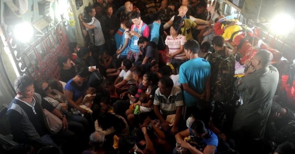 29.nov.2013 - Sobreviventes do tufão Haiyan a bordo de um avião militar C-130 deixam Tacloban, em direção à Manila, capital das Filipinas, nesta sexta-feira (29)