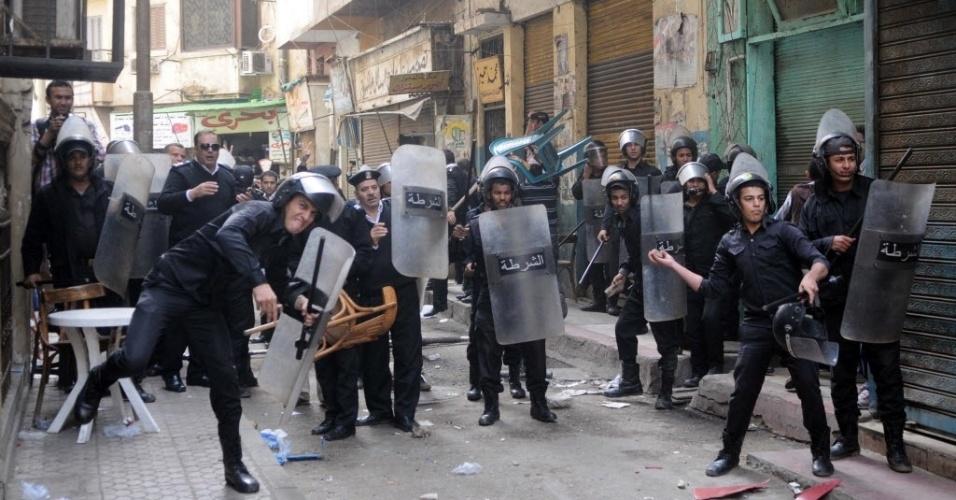 30.nov.2013 - Policiais egípcios atiram pedras durante confronto com manifestantes no Cairo. Eles protestam contra a nova lei que exige autorização oficial para a realização de manifestações