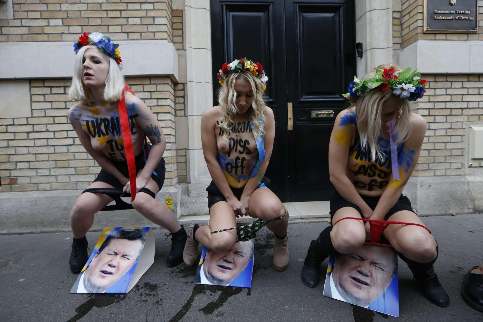 01.dez.2013 - Ativistas do grupo feminista Femen urinam em fotos do presidente ucraniano, Viktor Yanukovych, em frente à embaixada do país em Paris, na França. Neste domingo, mais uma vez manifestantes foram às ruas de Kiev para protestar contra o presidente da Ucrânia, acusado de vetar o ingresso no país na União Europeia